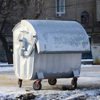A silver garbage container stands near residential buildings in winter