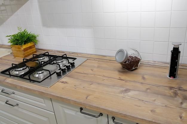 木製のキッチンセットの表面にある銀のガスストーブ