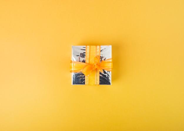 노란색 배경에 리본으로 장식 된 실버 선물 상자