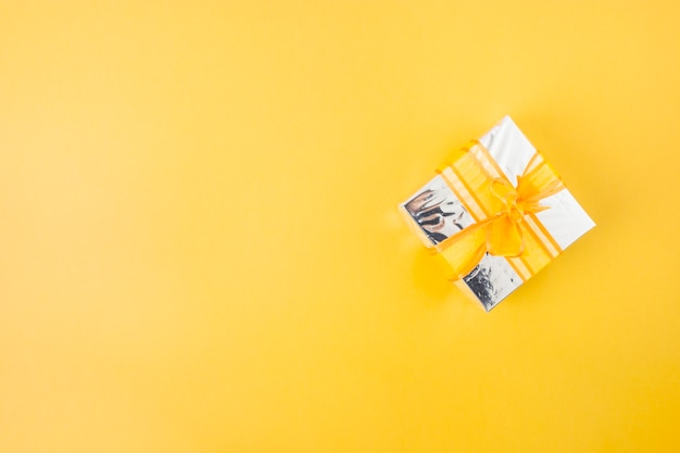 Silver gift box decorated with yellow ribbon over the yellow background