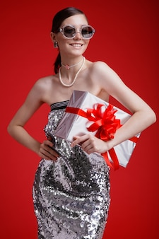Silver gift box red bow elegant woman in sequin dress sunglasses accessories on red background