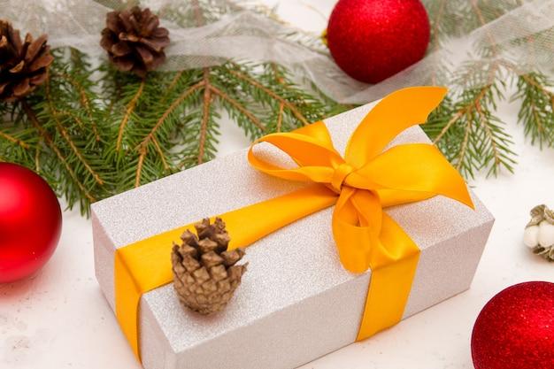 背景、新年の背景に金のリボンの弓、モミの枝、コーン、クリスマスボールと銀のギフトボックス