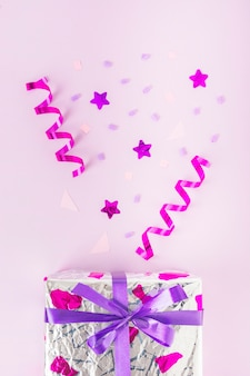 Silver gift box with curled streamers, star shape and confetti against pink background