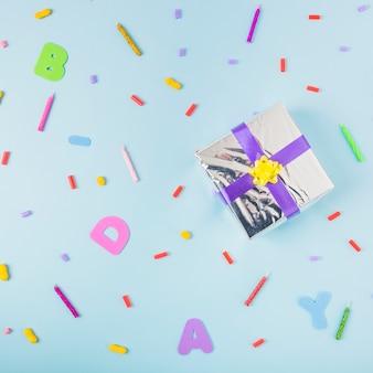 Contenitore di regalo d'argento con nastro viola e giallo su sfondo blu disordinato