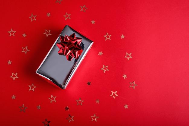 Серебряная подарочная коробка с красным бантом с блестками золотых звезд на красном фоне с копией пространства