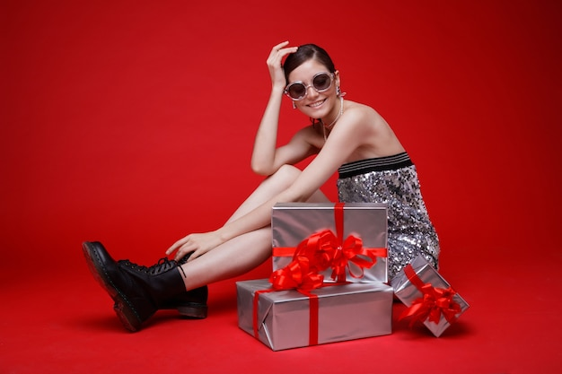 Silver gift boxes red bows woman in sequin dress sunglasses boots accessories red background