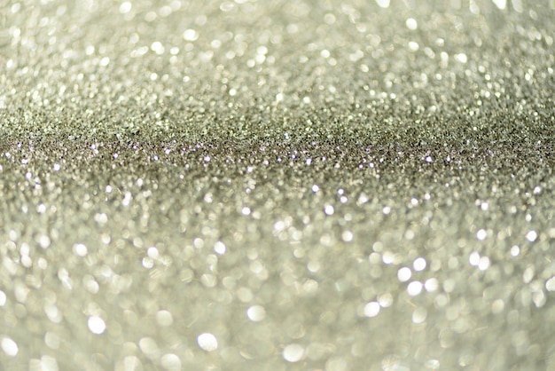 Silver glitter background with abstract bokeh lights.