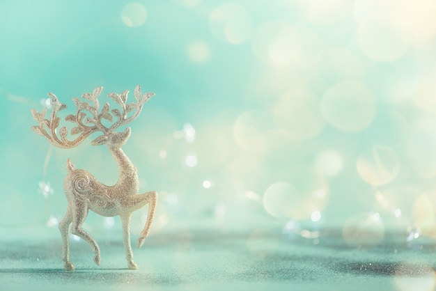 Silver glitter christmas deer on blue background with lights bokeh, copy space.