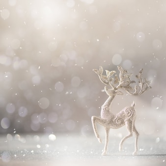 Silver glitter christmas deer on grey background with lights bokeh, copy space.