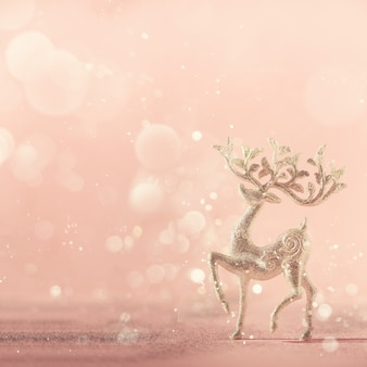 Silver glitter christmas deer on pink background with lights bokeh, copy space.