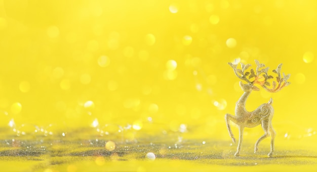 Silver glitter christmas deer on yellow background with lights bokeh, copy space.