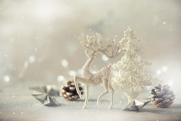Silver glitter christmas tree, deer, cones on grey background with lights bokeh, copy space.