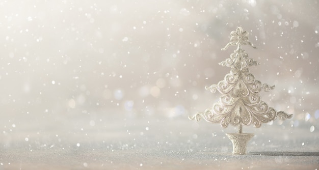 Silver glitter christmas tree on grey background with lights bokeh, copy space.