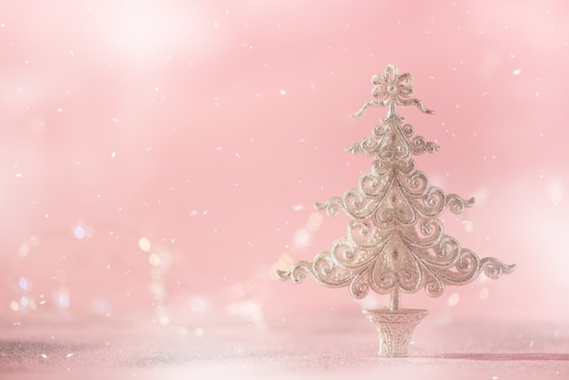 Silver glitter christmas tree on pink background with lights bokeh, copy space.