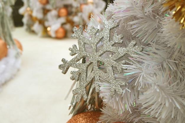 Silver glitter snowflake ornament on white christmas tree