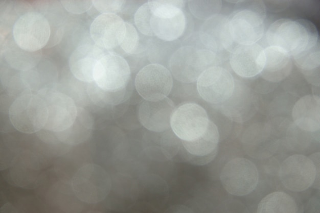Silver glittering christmas lights bokeh. blurred abstract background