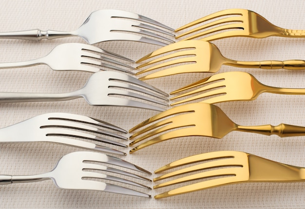 Silver and gold forks on a light background. silverware, kitchen utensils