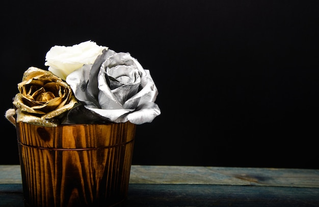 Silver and gold fresh rose flower in wooden vase. grunge beauty. luxury and success. metallized antique decor. richness. floristics business. vintage & retro copy space. greeting card gift.