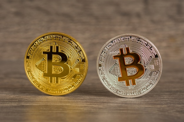 Silver and golden bitcoin mettallic coins on wooden table