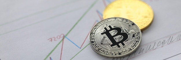Silver and golden coin of bitcoin lie on business