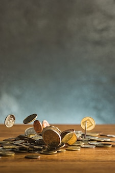 The silver and golden coins and falling coins on wooden table