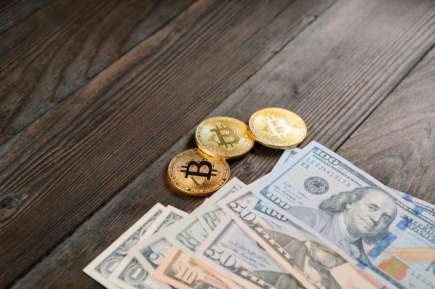Silver and golden coins with bitcoin, ripple and ethereum symbol on wood background.
