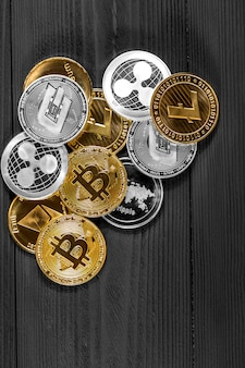 Silver and golden coins with bitcoin, ripple and ethereum symbol on wood.