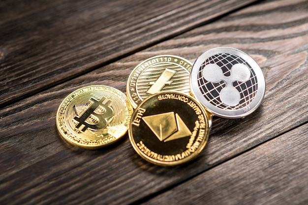Silver and golden coins with bitcoin, ripple and ethereum symbol