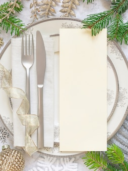 Silver and golden festive table setting with christmas ornaments and  blank card template
