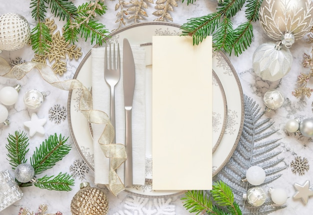 Silver and golden festive table setting with ornaments and fir branches with blank card