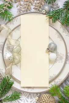 Silver and golden festive table setting with ornaments and fir tree branches with blank card