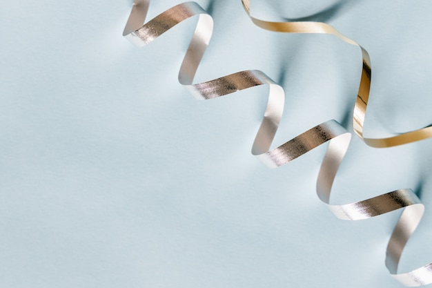Silver and golden festive ticker tape decoration on pastel blue background. holidays modern minimalistic concept.