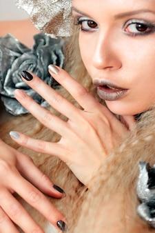 Серебристо-серый бежевый макияж и маникюр для девушки модели крупным планом с волнистыми волосами.
