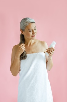 Silver haired middle aged asian woman looks at body care product on pink background