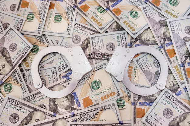 銀の手錠と米ドル、犯罪の概念。