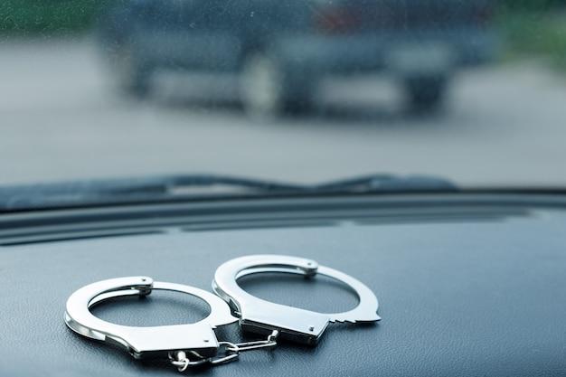 На панели автомобиля лежат серебряные наручники. дорожные преступления. фото высокого качества