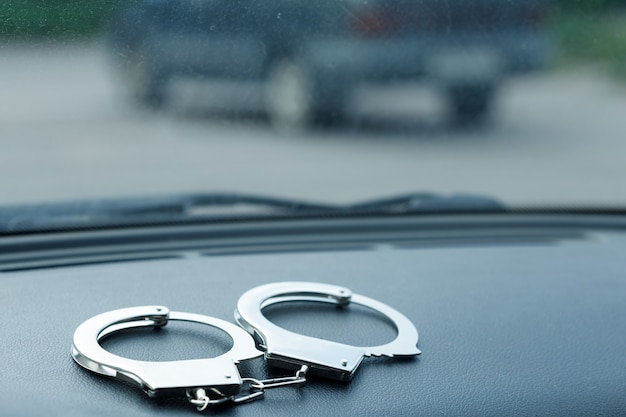 Silver handcuffs lie on the panel of the car. road crimes. high quality photo