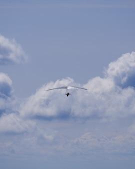 雲の背景にシルバーハンググライダー