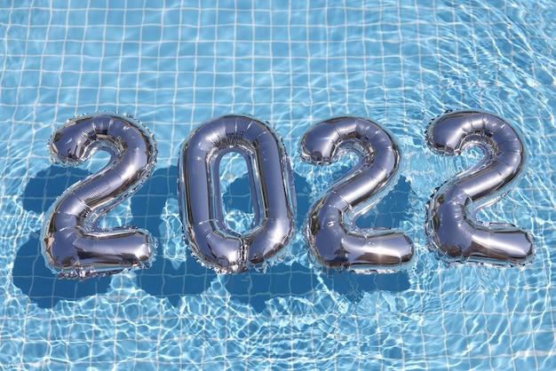 スイミングプールのクローズアップの背景に浮かぶ数字と銀のヘリウム風船