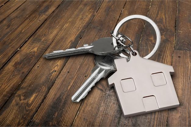 Серебряный ключ от дома со значком на деревянном столе