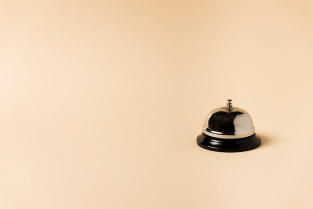 Silver hotel doorbell, with beige background