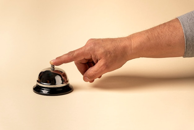 Silver hotel doorbell, with human hand touching it with beige background