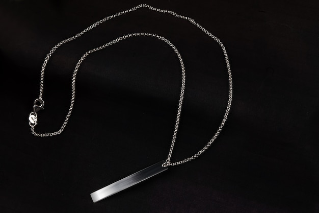 Silver jewelry chain bracelet necklace isolated on black background with engraving plate