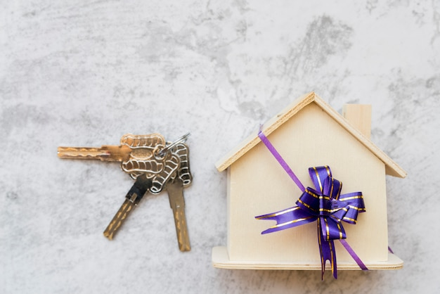 Silver keys near the house wooden model with ribbon bow on white concrete wall