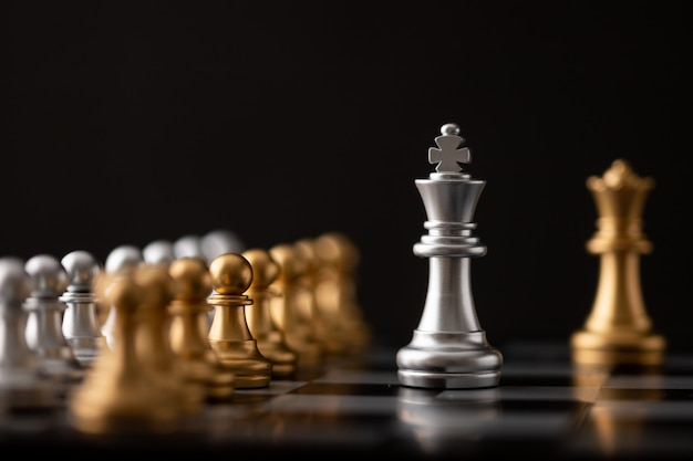 Silver king and gold queen on chessboard