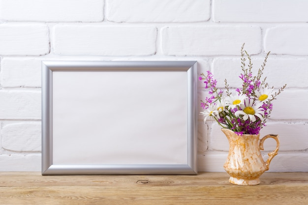 Silver landscape frame  with chamomile and purple flowers in golden pitcher