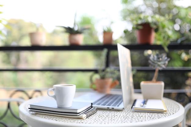 Серебряный ноутбук, вид сбоку, белый макет и чашка кофе с ноутбуками на белом столе на открытом воздухе