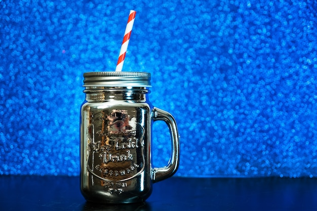 Silver mason jar with red straw on blue blurred glitter lights background