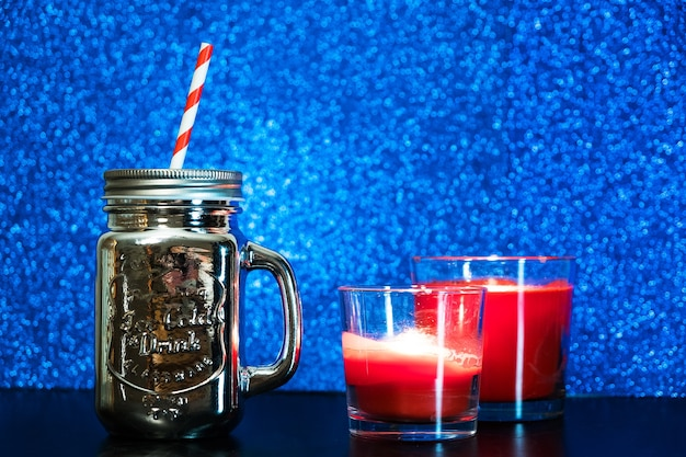 Silver mason jar with red straw on blue blurred glitter lights background.