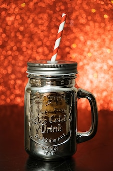 Silver mason jar with red straw on red blurred glitter lights background.